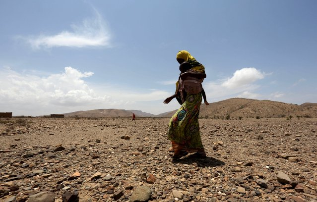 An internally displaced woman carries her child as they wait for assistance at Hariirad town of Awdal region, Somaliland April 9, 2016. (Photo by Feisal Omar/Reuters)