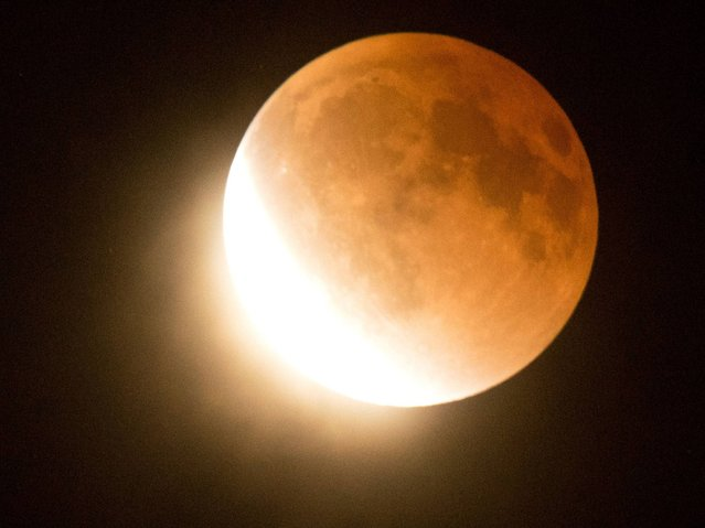 The moon moves out of a lunar eclipse over southern California as seen from Korea town, west of downtown Los Angeles. (Photo by Joe Klamar/AFP Photo)