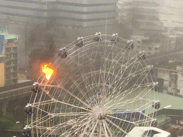 An empty passenger car of a Ferris wheel burns at a newly opened dinosaur theme park in central Bangkok, Thailand, Saturday, April 30, 2016. There were no reports of injuries and the cause of the fire, which was out largely because of a torrential downpour, is not known. (Photo by Shilpa Ko via AP Photo)