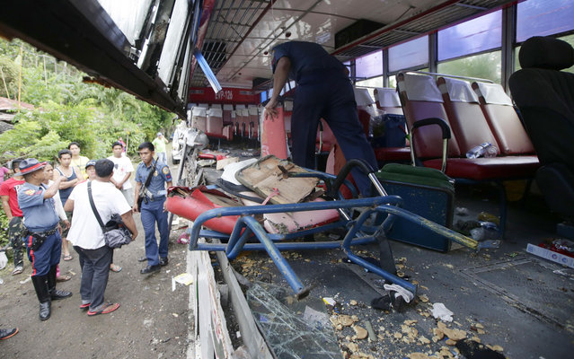 Police and rescuers inspect a passenger bus after it rammed into a cargo truck early Wednesday, April 16, 2014 along a highway at Libmanan township, Camarines Sur province, south of Manila, Philippines. Police said at least five passengers, including a child, were killed and 15 others were injured in the accident Wednesday which came as Filipinos flock to their hometowns for the Holy Week break. (Photo by Bullit Marquez/AP Photo)