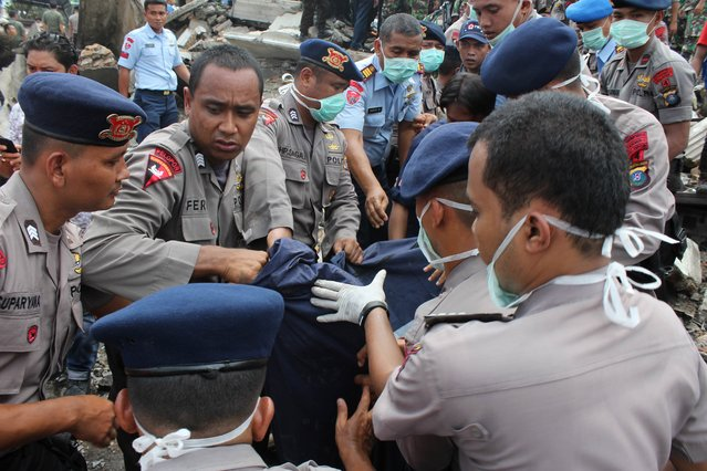 Indonesian rescue personnel retrieve a body from the scene of an Indonesian military C-130 Hercules aircraft crash in Medan on June 30, 2015. An Indonesian military transport plane crashed on June 30 shortly after take-off in a city on Sumatra island, exploding in a ball of flames in a residential area. (Photo by AFP Photo/ATAR)