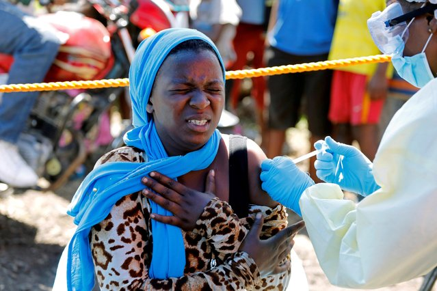 A young woman reacts as a health worker injects her with the Ebola vaccine, in Goma, Democratic Republic of Congo, August 5, 2019. Congolese authorities are racing to contain the epidemic after a gold miner with a large family spread Ebola in the east's main city of Goma. (Photo by Baz Ratner/Reuters)