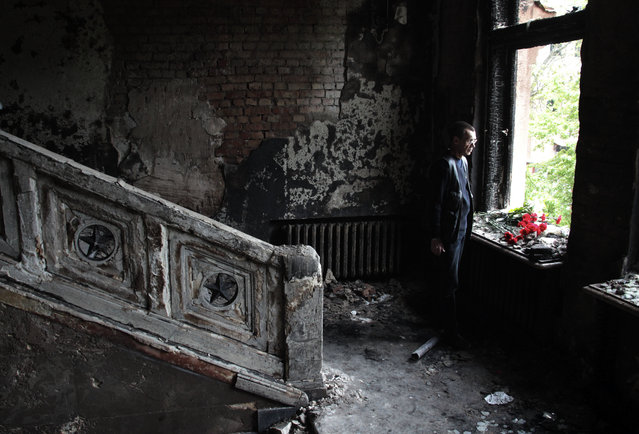 In this Sunday May 4, 2014 file photo, a man lays flowers inside the burnt trade union building in Odessa, Ukraine. Demonstrators have gathered in the Ukrainian city of Odessa to mark the second anniversary of the street clashes that culminated in a fire that killed 43 people as they took shelter from opponents. (Photo by Sergei Poliakov/AP Photo)