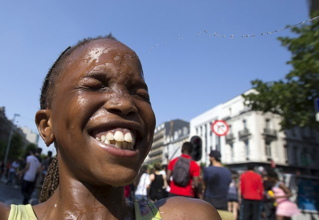 A girl smiles while taking part in a giant water fight on a hot summer day in central Brussels, Belgium, July 3, 2015. (Photo by Yves Herman/Reuters)
