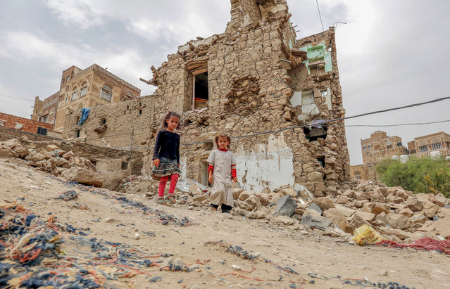 Yemeni children look on at the site of a historic building destroyed by a previous Saudi-led airstrike, in the old city of Sana'a, Yemen, 07 July 2019. According to reports, UNESCO has added two cities in Yemen to the List of World Heritage in Danger, including the historic city of Sana'a which is a dense warren of centuries-old mud-brick houses, due to the damage caused to the cultural heritage of Sana'a as a result of ongoing armed conflict in Yemen since March 2015. Sana'a, listed as a world heritage site by UNESCO in 1986, has been inhabited for more than 2,500 years. It is made up of some 8,000 buildings, including its distinctive multi-story tower houses, most of them are between 200 and 500 years old. (Photo by Yahya Arhab/EPA/EFE)