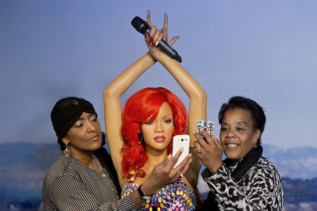 """In this Wednesday, April 23, 2014 photo released by Madam Tussaud's, Trevar Booker of the Fisherman's Wharf Association, left, and Karmen Bell of the San Francisco Travel Association take a """"selfie"""" photo with a wax figure of Rihanna on display at the future site of Madame Tussaud's attraction at Fisherman's Wharf in San Francisco. (Photo by Beck Diefenbach/AP Photo/Madam Tussaud's)"""
