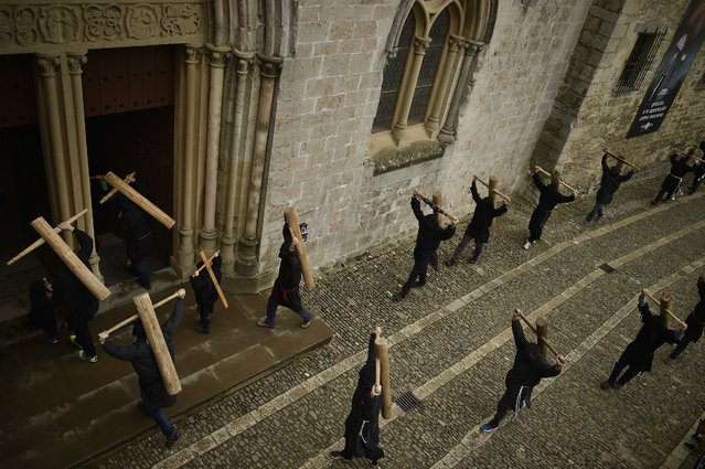 """Masked penitents hold their crosses as they arrive at Roncesvalles Church during spring """"Romeria Cruceros de Arce"""", in northern Spain, Sunday, May 8, 2016. Every year on the second Sunday in spring, people with crosses march from their small Pyrenees towns to Roncesvalles Church in tribute of the Virgin. (Photo by Alvaro Barrientos/AP Photo)"""