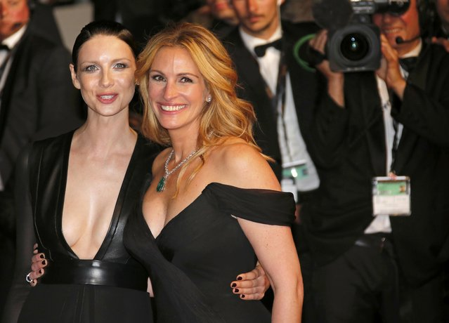"""Cast members Julia Roberts and Caitriona Balfe pose on the red carpet after the screening of the film """"Money Monster"""" out of competition at the 69th Cannes Film Festival in Cannes, France, May 12, 2016. (Photo by Jean-Paul Pelissier/Reuters)"""