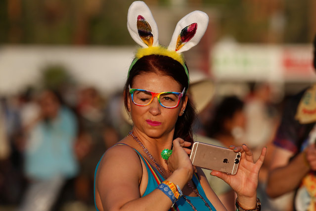 A woman walks with bunny ears in the late afternoon sun during the Coachella Valley Music and Arts Festival on April 17, 2017 in Indio, California. (Photo by Carlo Allegri/Reuters)