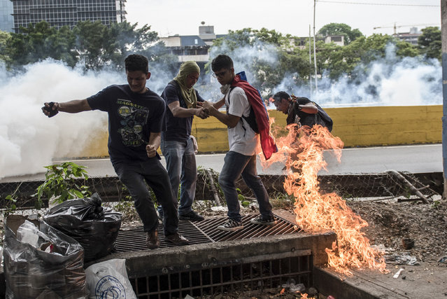 Demonstrators clash with the riot police during a protest against Venezuelan President Nicolas Maduro, in Caracas on April 20, 2017. (Photo by Carlos Becerra/AFP Photo)