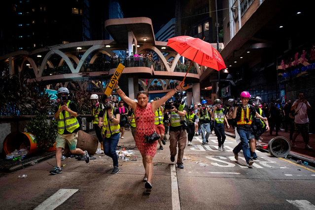 """A woman holds up an umbrella and license plates, one that reads """"love"""", during violent protests between riot police and demonstrators in the Causeway Bay district of Hong Kong on October 1, 2019. The city observes the National Day holiday to mark the 70th anniversary of communist China's founding Strife-torn Hong Kong on October 1 marked the 70th anniversary of communist China's founding with defiant """"Day of Grief"""" protests and fresh clashes with police as pro-democracy activists ignored a ban and took to the streets across the city. (Photo by Nicolas Asfouri/AFP Photo)"""