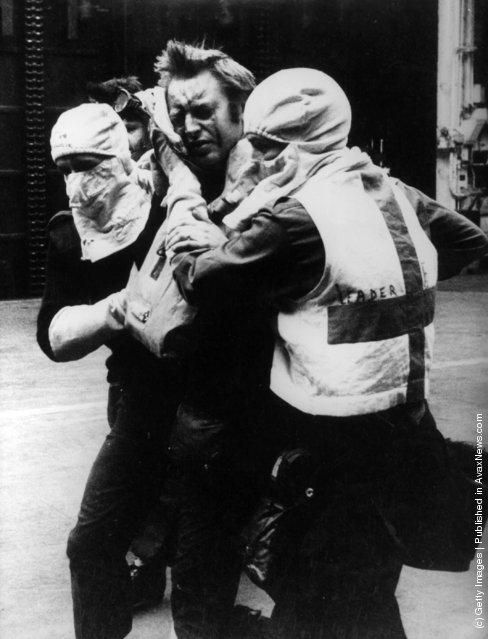 Medical orderlies wearing anti-flash gear tend a wounded survivor of HMS Sheffield aboard HMS Hermes during the Falklands War