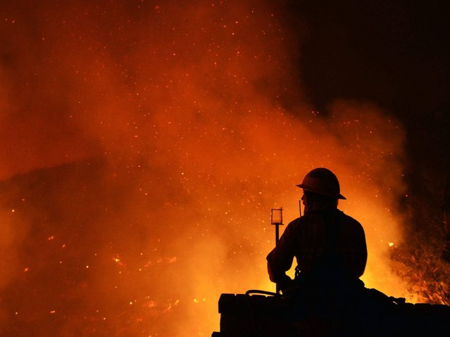 A firefighter on structure defense duty watching flames in San Marcos, San Diego county, California. (Photo by Stuart Palley/EPA)