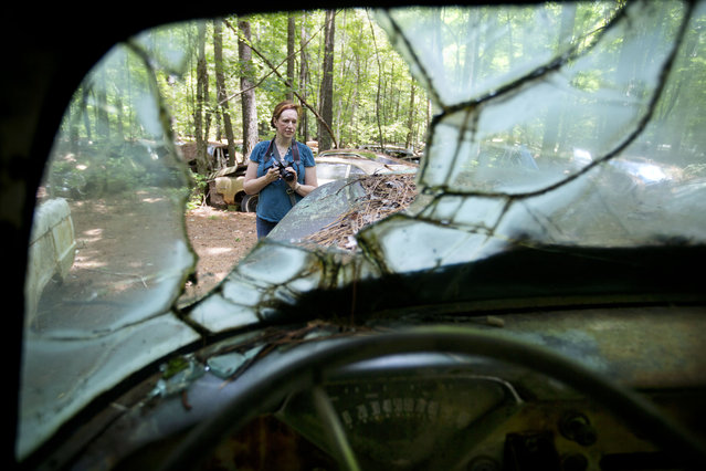 Judith Kimber, of Belfast, Northern Ireland, takes photos while walking through Old Car City, the world's largest known classic car junkyard Thursday, July 16, 2015, in White, Ga. (Photo by David Goldman/AP Photo)