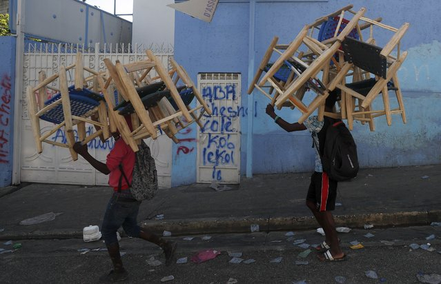 Chair vendors carry their wares past a street market where businesses have often closed in recent days as protests calling for President Jovenel Moise to resign roil the area in Port-au-Prince, Haiti, Tuesday, October 1, 2019. Opposition leaders and supporters say they are angry about public corruption, spiraling inflation and a dwindling supply of gasoline that has forced many gas stations in the capital to close. (Photo by Rebecca Blackwell/AP Photo)