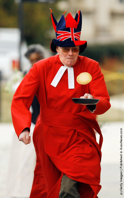Canon Ralph Godsall, priest vicar at Westminster Abbey in London, participates in his first pancake race during the Shrove Tuesday, or Mardi Gras, tradition at the National Cathedral