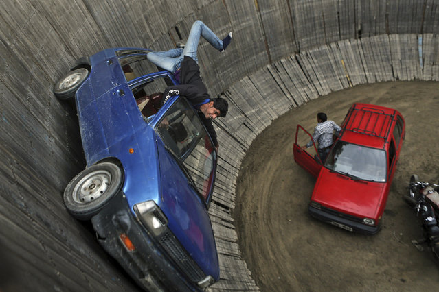 "A stuntman performs in a car at the ""Well of Death"" at an exhibition in Srinagar, India, Friday, May 23, 2014. In the Well of Death, stunt drivers on motorbikes and cars drive in circles around the vertical walls of the well-shaped construction. (Photo by Dar Yasin/AP Photo)"