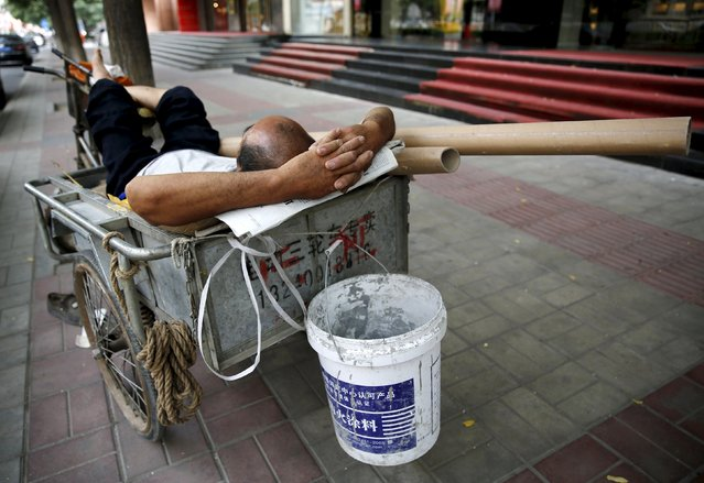 A man takes a nap in a tricycle on a street at a financial district in Beijing, China, July 10, 2015. The plunge in China's previously booming stock markets, which had more than doubled in the year to mid-June, has created a major headache for President Xi Jinping and China's top leaders, who are already grappling with slowing growth. (Photo by Kim Kyung-Hoon/Reuters)
