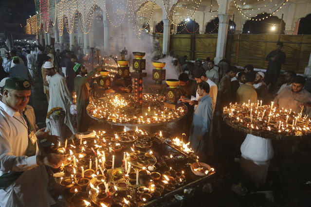 People light oil lamps during the three-day annual festival of saint Al-Sheikh Ali Bin Usman Al-Hajveri known as Data Ganjbaksh, at his shrine, in Lahore, Pakistan, Friday, October 18, 2019. Thousands of people traveled from all over Pakistan to attend the annual celebrations. (Photo by K.M. Chaudary/AP Photo)