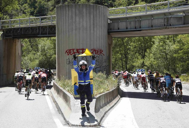 A French gendarme uses a yellow flag to advise a danger as riders cycle during the 161-km (100 miles) 17th stage of the 102nd Tour de France cycling race from Digne-les-Bains to Pra Loup in the French Alps mountains, France, July 22, 2015. (Photo by Eric Gaillard/Reuters)
