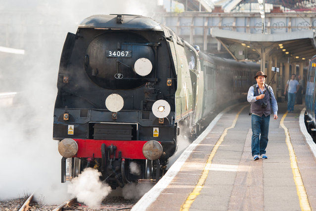 """Steam enthusiast David Crosby, from Brisbane, Australia, uses a selfie stick to take a photo with """"Tangmere"""", a 1947 Battle of Britain class Pacific 4-6-2 steam locomotive, pulling the Dorset Coast Express train to Weymouth at Victoria station, London, Wednesday July 22, 2015. The Railway Touring Company operate summer steam services from London to the Dorset coast, using steam locomotives built in the 1940's and1950's. (Photo by Dominic Lipinski/PA via AP Photo)"""