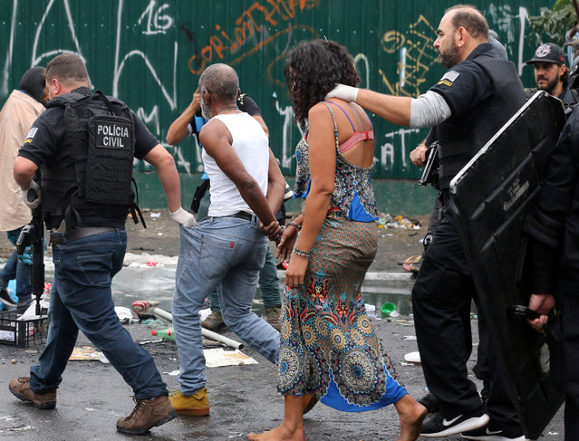 Riot police detain people during a police operation in a neighborhood known to locals as Cracolandia (Crackland), in downtown Sao Paulo, Brazil May 21, 2017. (Photo by Paulo Whitaker/Reuters)
