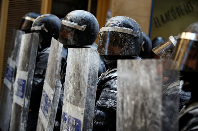 """Catalan regional police in full riot gear are covered in flour which was thrown by protesters during a protest over the eviction of squatters earlier in the week from """"The Expropriated Bank"""", in Barcelona, Spain, May 29, 2016. (Photo by Albert Gea/Reuters)"""