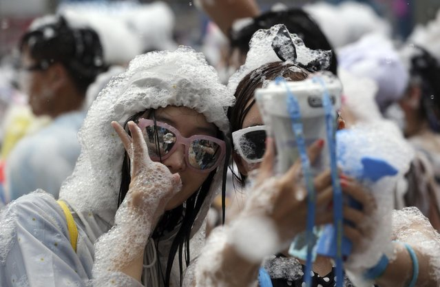 Participants are covered by bubbles as they take a selfie with a smartphone during the 3rd Water Gun Festival in Seoul, South Korea, Sunday, July 26, 2015. (Photo by Lee Jin-man/AP Photo)