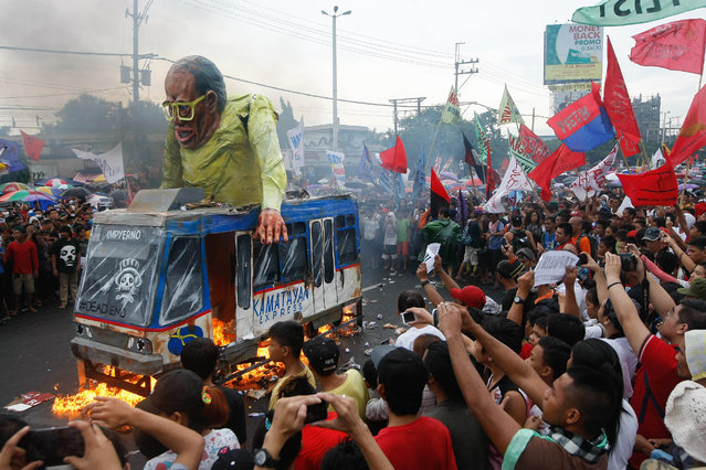 Protesters set a giant effigy of Philippine President Benigno Aquino III on fire during a rally to coincide with Aquino's last State-of-the-Nation-Address or SONA at suburban Quezon city northeast of Manila, Philippines, Monday, July 27, 2015. (Photo by Alecs Ongcal/AP Photo)