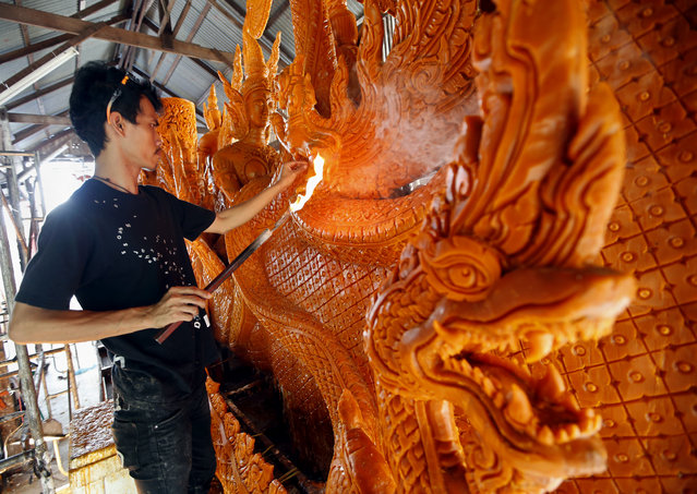Thai worker gives final touch to an ornately-carved bee wax candle depicting scene from the Buddhist mythology in preparation for a candle procession parade to mark the start of the Buddhist Lent, at a temple in the Ubon Ratchathani province, northeastern Thailand, July 28, 2015. The Buddhist Lent or 'Khao Pansa' is a three-month long period beginning on the first day after the full moon of the eight lunar month which this year falls on July 31. (Photo by Rungroj Yongrit/EPA)