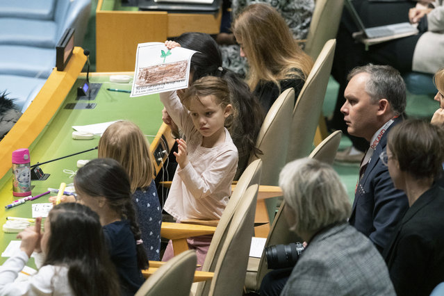 A young member of the Polish delegation shows off a drawing she made during the 30th anniversary of the adoption of the Convention on the Rights of the Child, Wednesday, November 20, 2019, at United Nations headquarters. (Photo by Mary Altaffer/AP Photo)