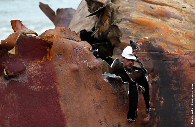 A workman cuts the hull of the TK Bremen into pieces on Kerminihy beach, on January 23, 2012