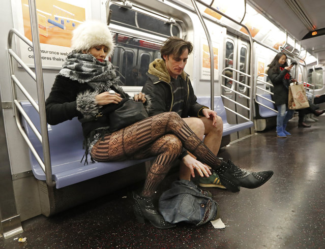 Leon Feingold, right, drops his jeans as his girlfriend Patrizia Calvio looks in her purse on the uptown E Train during the 18th annual No Pants Subway Ride, January 13, 2019, in New York. (Photo by Kathy Willens/AP Photo)
