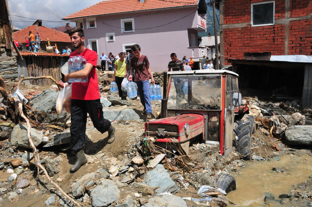 People, carry food and water, past a tractor stuck in  mud, stones and debris that were piled in a flood in the mountain village of Sipkovica, just above the town of Tetovo, in northwestern Macedonia, on Tuesday, August 4, 2015. (Photo by Zoran Andonov/AP Photo)
