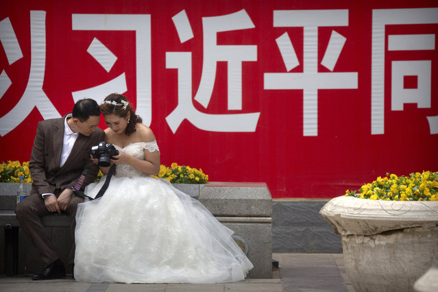 """In this May 19, 2018, file photo a couple in wedding dress look at photos on the back of a camera near a propaganda slogan with the name of Chinese President Xi Jinping in Beijing. Chinese leaders have long been sensitive about their communist country's international image. Now, they are battling back, investing in diplomacy and a courtship of hearts and minds, just as the United States digs in on the Trump administration's """"America First"""" mindset. (Photo by Mark Schiefelbein/AP Photo/File)"""
