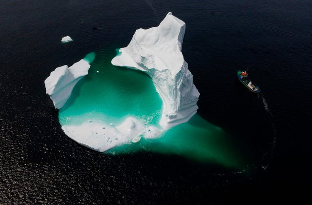 This aerial photo shows the boat of Captain Edward Kean passing an iceberg in Bonavista Bay on June 29, 2019 in Newfoundland, Canada. The abundance of icebergs, which continue to venture further into Canadian waters, has created a new form of tourism, iceberg sightseeing. In 2018, more than 500,000 tourists visited the province of Newfoundland, contributing nearly 570 million Canadian dollars (389 million euros) to the local economy, according to the estimates of the provincial government. (Photo by Johannes Eisele/AFP Photo)