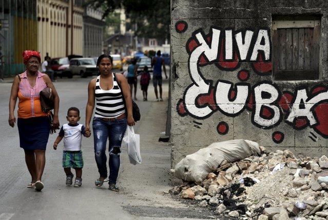 "People walk near graffiti that reads ""Long live Cuba"" in Havana April 11, 2015. (Photo by Enrique De La Osa/Reuters)"