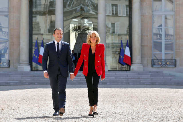 French President Emmanuel Macron and his wife Brigitte Macron walk toward the Elysee Palace courtyard, to welcome autistics people, prior to the launching of a program to enhance the diagnosis and treatment of autism, in Paris, France, July 6, 2017. (Photo by Thibault Camus/Reuters)