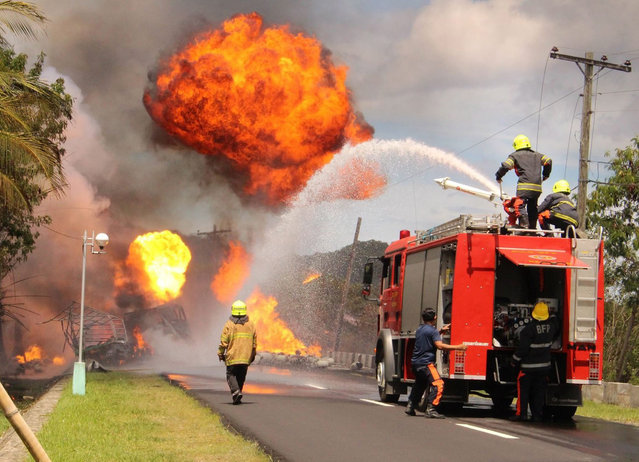 Filipino firemen try to extinguish burning Liquified Petroleum Gas (LPG) containers on a street in Baybay city, Leyte island, Philippines, 17 June 2016. A delivery truck carrying Liquified Petroleum Gas (LPG) tanks exploded while on its way to Maasin City, causing long lines of stranded motorists for hours. Nobody was hurt, according to local news. (Photo by Robert Dejon/EPA)