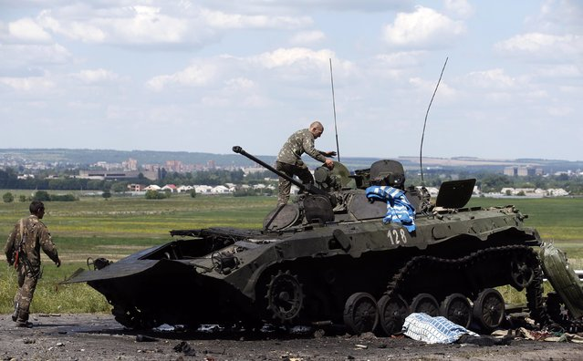 Ukrainian soldiers check a destroyed armoured vehicle at a Ukrainian Army checkpoint in the outskirts of the eastern Ukrainian town of Slaviansk July 5, 2014. Pro-Russian rebels were pulling out of a flashpoint area of eastern Ukraine on Saturday as authorities in Kiev savored a major military success in its three-month fight against the separatists. (Photo by Maxim Zmeyev/Reuters)