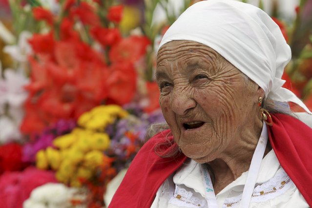 A flower grower, known as a silletero, looks at flower arrangements as she participates in the annual flower parade in Medellin, Colombia, August 9, 2015. (Photo by Fredy Builes/Reuters)