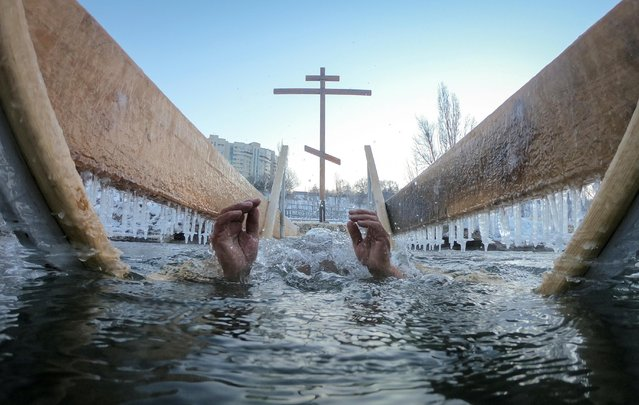 A man takes a dip in icy waters of the Bolshaya Almatinka river during Orthodox Epiphany celebrations in Almaty, Kazakhstan on January 19, 2020. (Photo by Pavel Mikheyev/Reuters)
