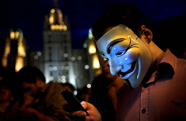 A masked protester tweets while listening to a speech at a new campsite for opponents of the government in Moscow on May 18, 2012