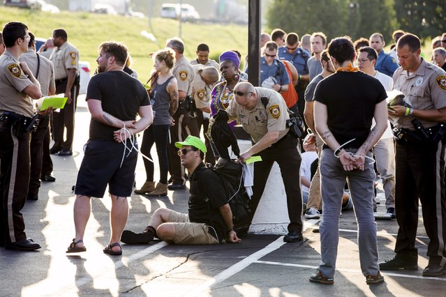 "Officers from the St Louis County Police Department and the Missouri Highway Patrol process demonstrators from the ""Black Lives Matter"" movement, who had been arrested for protesting on Interstate 70, in Earth City, Missouri August 10, 2015. (Photo by Lucas Jackson/Reuters)"