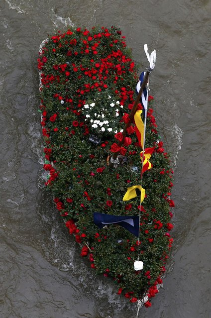 """Yorkshire Rose"", a boat filled with flowers in memory of murdered Labour Party MP Jo Cox, who was shot dead in Birstall, is towed down the River Thames in London, Britain June 22, 2016. (Photo by Neil Hall/Reuters)"