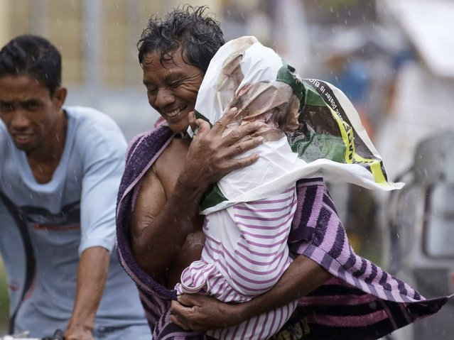 Residents of the slum community of Baseco evacuate to safer grounds at the onslaught of typhoon Rammasun in Manila Wednesday, July 16, 2014 in Manila, Philippines. Typhoon Rammasun left at least seven people dead and knocked out power in many areas Wednesday but the Philippine capital and densely populated northern provinces were spared a direct battering when its fierce winds shifted slightly. (Photo by Bullit Marquez/AP Photo)