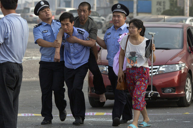Chinese police help a man to safety near the site of explosions in northeastern China's Tianjin municipality, Thursday, August 13, 2015. (Photo by Ng Han Guan/AP Photo)