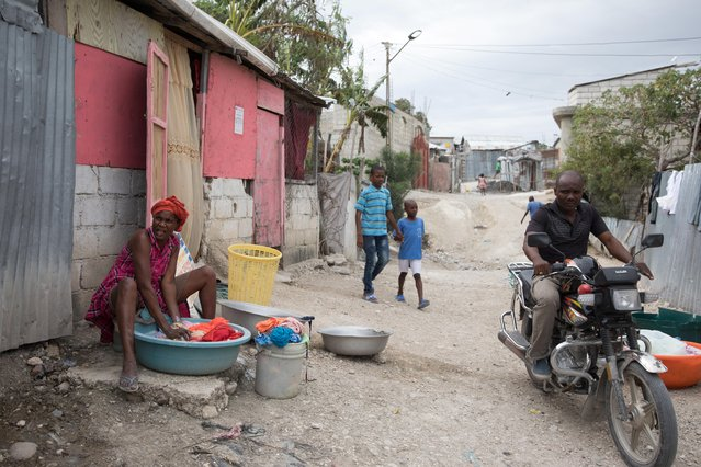A man drives a bike past a woman doing laundry in a street of Caradeux, a camp for people displaced by the January 2010 earthquake, in Port-au-Prince, January 10, 2020. In Haiti, a country that was extremely poor even before the earthquake, nearly 60% of the population survives on less than $2.40 a day. Due to a combination of weather, geography and sub-standard construction, Haiti is particularly vulnerable to natural disasters, which have eroded progress. (Photo by Valerie Baeriswyl/Reuters)