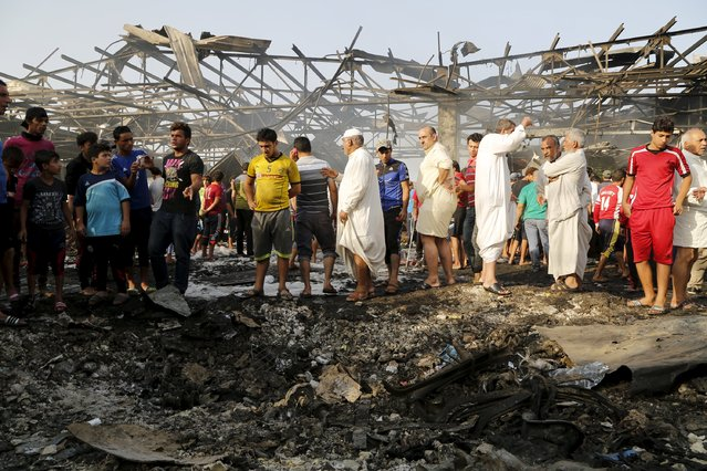 Residents gather at the site of a truck bomb attack at a crowded market in Baghdad August 13, 2015. At least 60 people were killed and 200 wounded on Thursday when a refrigerated truck packed with explosives blew up in a crowded market in Sadr City, a Shi'ite district in northeastern Baghdad, police and medical sources said. (Photo by Wissm Al- Okili/Reuters)