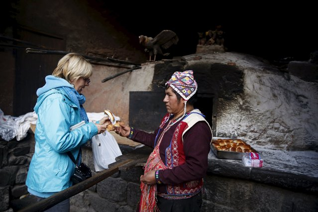 Baker Eulogio Pillco sells traditional empanadas that he baked using an oven made of clay to a tourist in the town of Pisac, Cusco, August 13, 2015. (Photo by Pilar Olivares/Reuters)